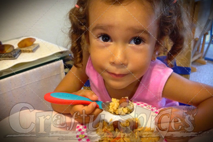 Kira enjoying Locrio de Salchichas y Gandules Verdes con Coco a great Dominican favorite