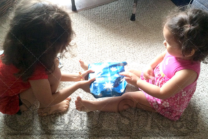 Kira handing over a gift to her baby sister