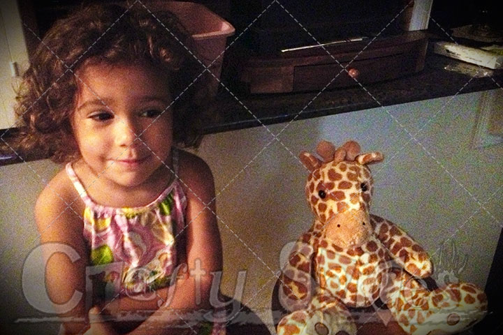 Kira and baby Giraffe sitting next to each other.